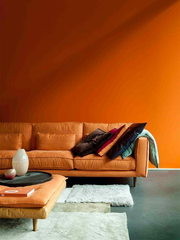 Màu sơn tường phối với sofa màu cam trong một phòng khách